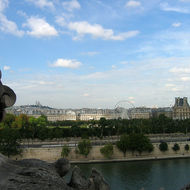 A view from the upper floor of the Orsay Museum, looking across the Seine to the Tuileries and the Louvre, with the Basilica of Sacrè Cœur in the distant background.
