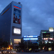 A view of downtown Seoul, with one of many large TV monitors on the side of a hotel (the Koreana).