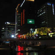 A view of downtown Seoul from the Cheonggye Stream -- notice the large TV monitor (green) on the side of the highrise.