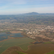 An aerial view of salt ponds in the San Francisco Bay, looking toward Mount Diablo in the distance.