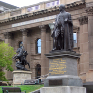 The exterior of the State Library of Victoria, Melbourne, with a statue of Sir Redmond Barry.
