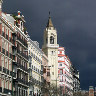 Buildings near the Puerta de Alcalá with storm clouds.