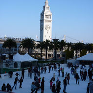 The winter ice rink at the Embarcadero Center in San Francisco, with the Ferry Building and the Bay Bridge in the background.