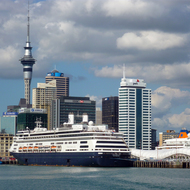 Downtown Auckland from a ferry, including a cruise ship in the foreground and the Sky Tower in the background.