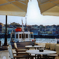 A boat moored beside a restaurant at the harbor of Chania, Crete.