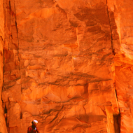 A river guide dwarfed by a side canyon wall in the Grand Canyon.