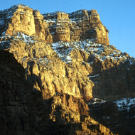 Snow dusted Grand Canyon cliffs in sunrise as seen from below.