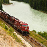 Canadian Pacific loco #8718 hauls freight eastwards beside the Bow River.
