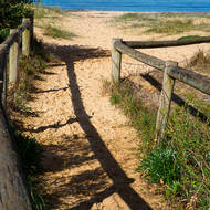 Fenced track to the beach and Phillip Island over Westernport bay.