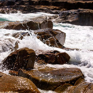 Waves breaking on the rocks and flying spray.
