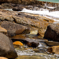 Rocky shore of Tea Tree Bay and across to the Great Sandy National Park.