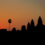 The sun rises over the west side of Angkor Wat.