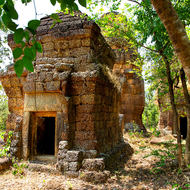 Set of three small laterite temples in the jungle.
