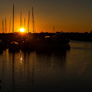 The setting sun is just a golden orb over the small boat harbor at Yamba.