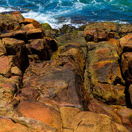 Swirling sea and slippery rocks on the point at South West Rocks.